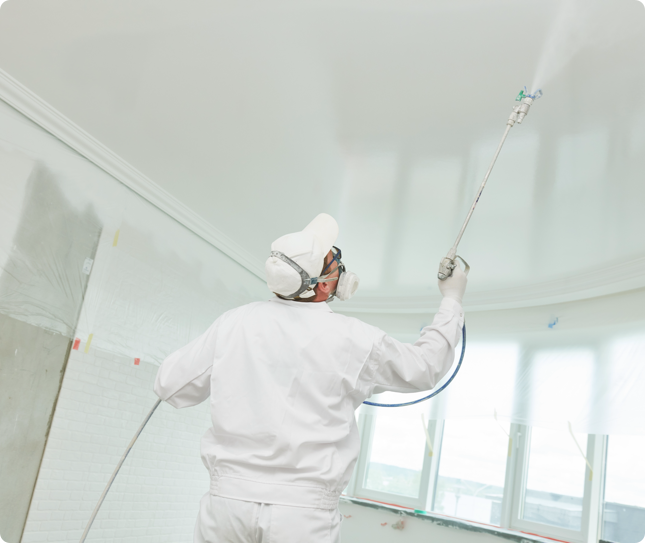 man applying a coat of white paint to the ceiling using the dry-fall painting method