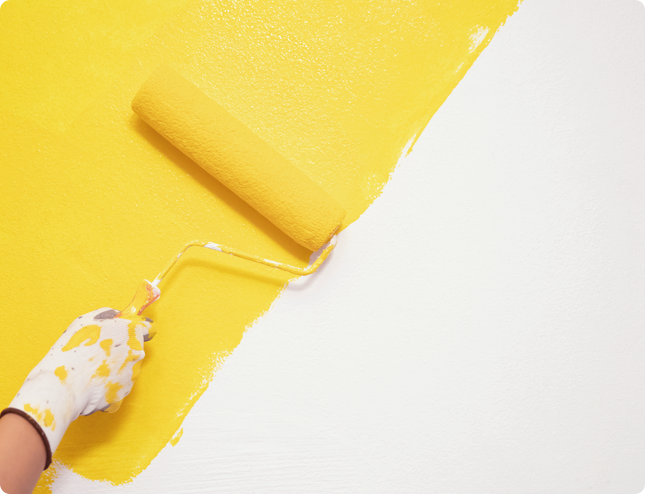 yellow paint being applied onto a blank wall with a paint roller