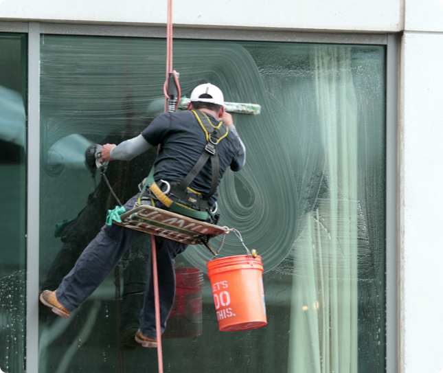 a man cleaning the windows on the exterior of a high-rise building