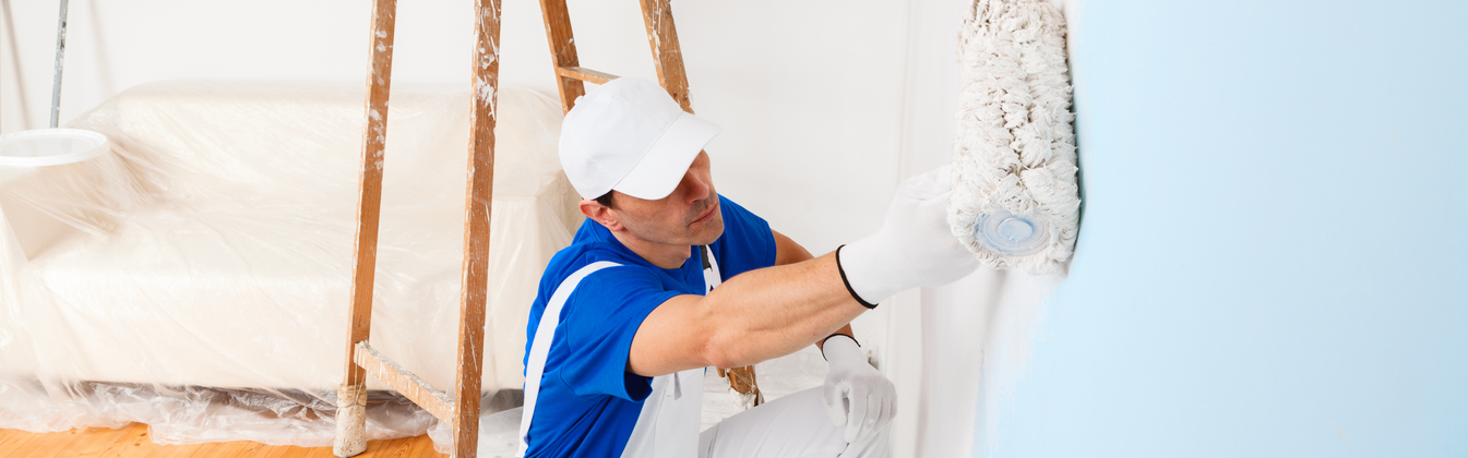 Professional interior painter using a roller brush