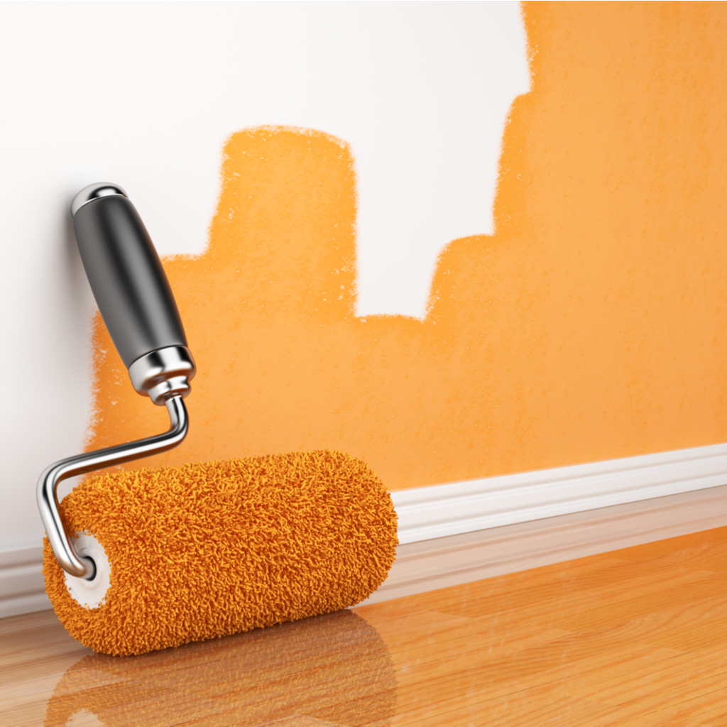 a partially orange painted wall with an orange paint roller laying nearby