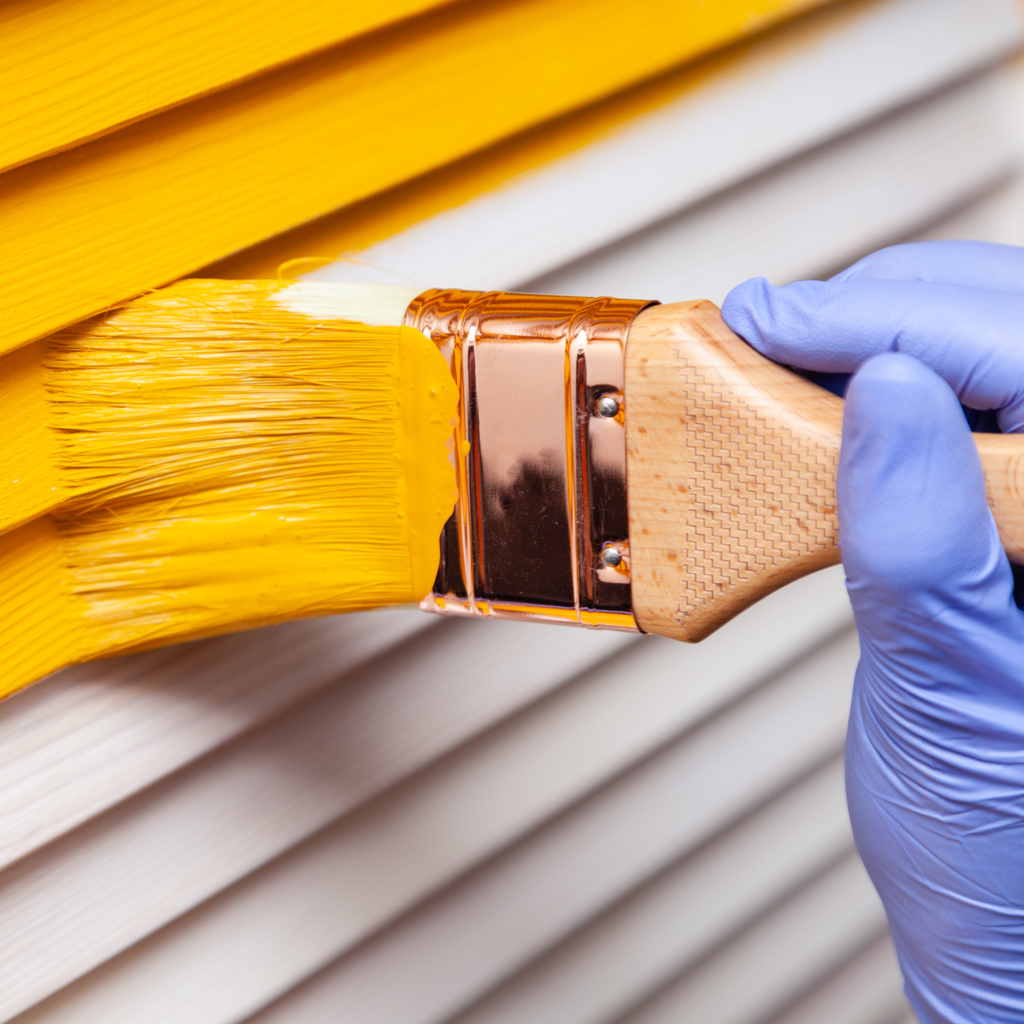 Person painting white wall yellow