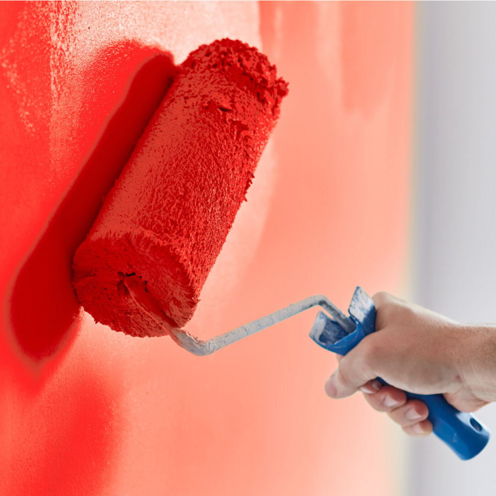 someone painting a wall red with a paint roller