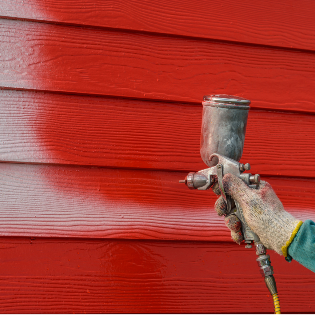 someone spraying red paint onto the exterior of a home