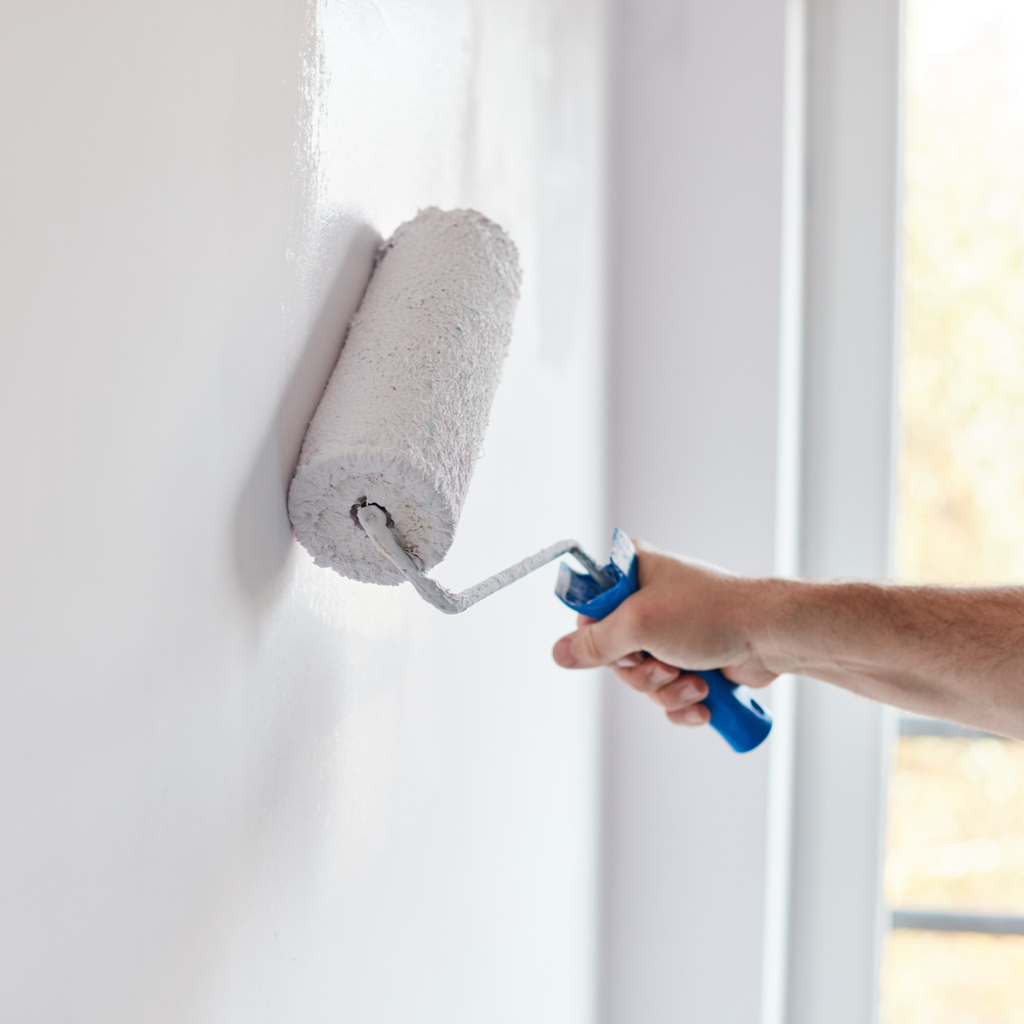 someone applying white paint on a wall inside their home with a paint roller