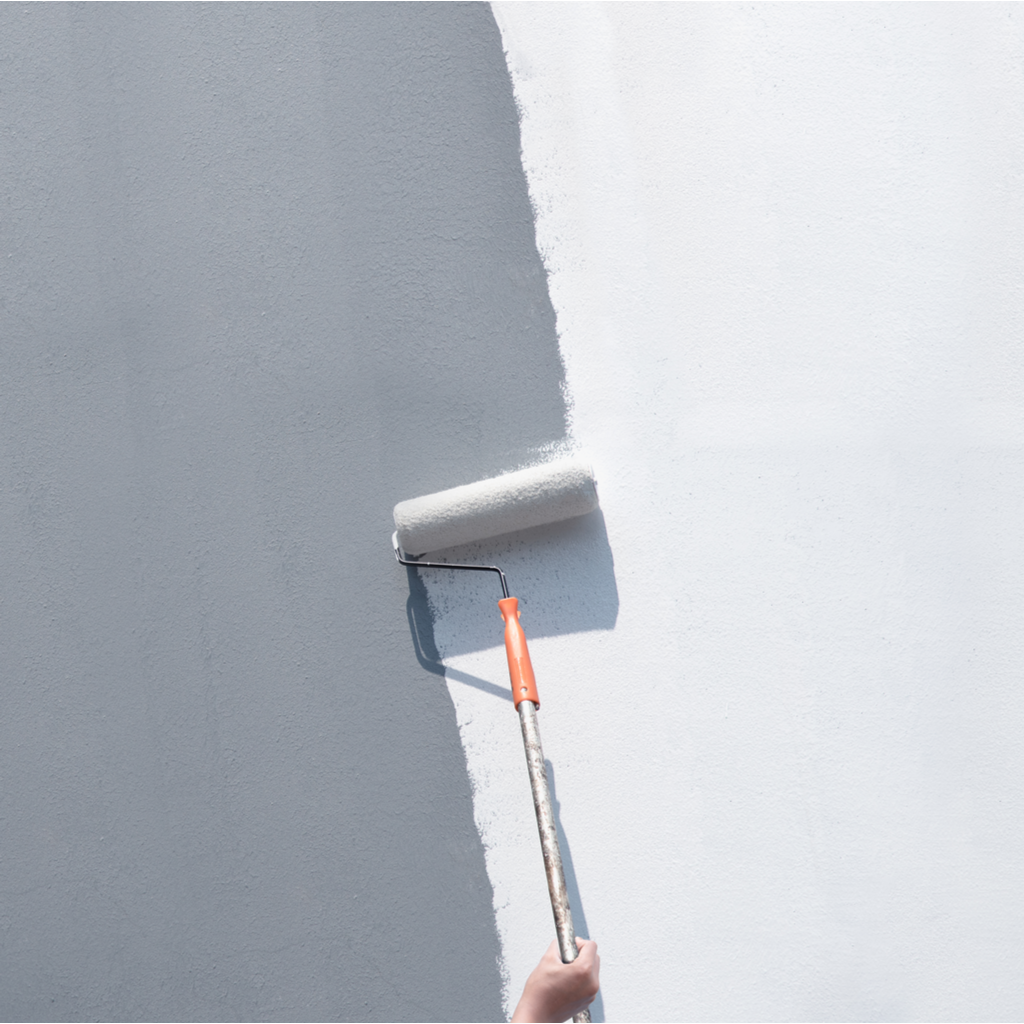 Person painting wall grey