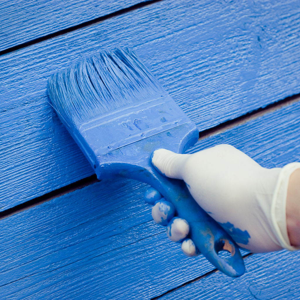 Person painting wood blue