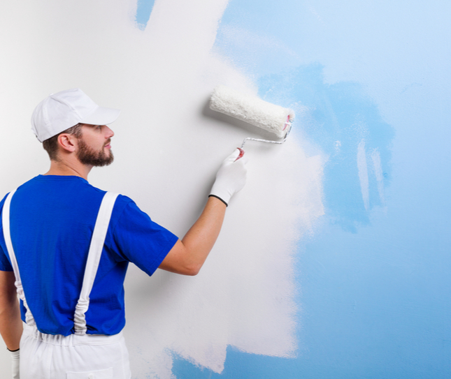Person painting blue wall white