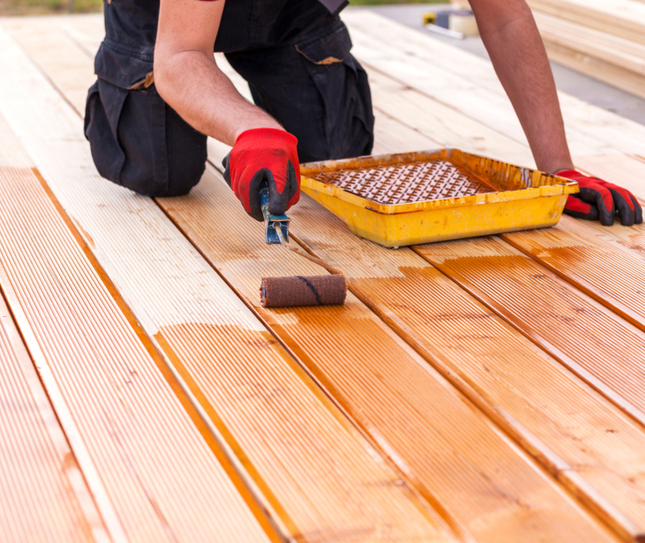 a man painting an outdoor deck