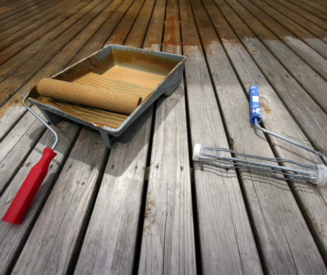 deck painting materials sitting on an unfinished deck