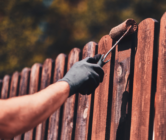 a man painting a fence