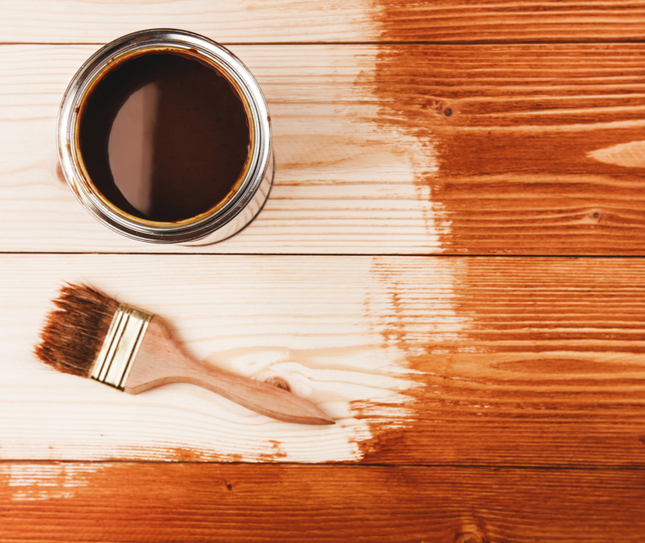 a can of stain and a brush sitting on a deck